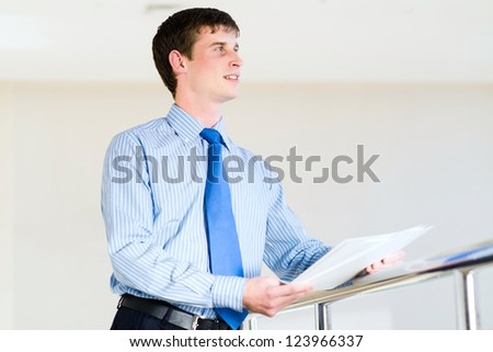 Portrait of a businessman standing in the office, keep the documents