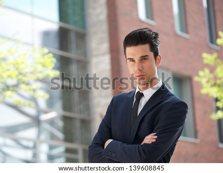 Portrait of a businessman standing outdoors with arms crossed - stock photo