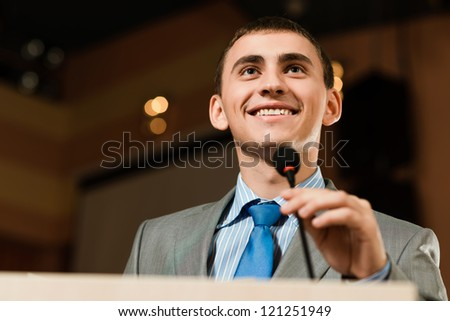 Portrait of a businessman standing with a microphone and looking ahead, speak at the conference - stock photo