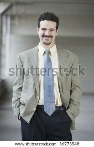 Portrait of a businessman standing with his hands in his pockets - stock photo