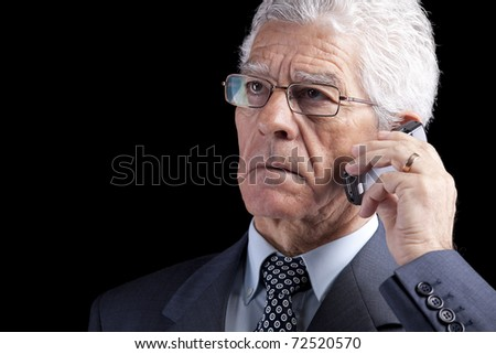 Portrait of a businessman talking at the mobile telephone (isolated on black) - stock photo