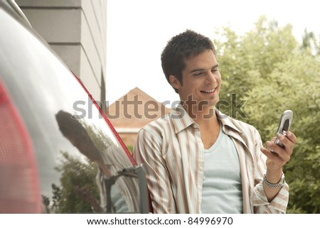 Portrait of a businessman texting with a cell phone, leaning on his car. - stock photo