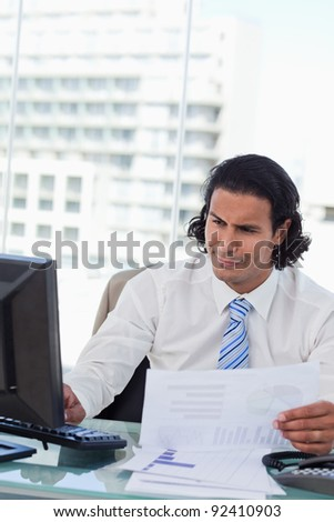 Portrait of a businessman using a computer while looking at statistics in his office