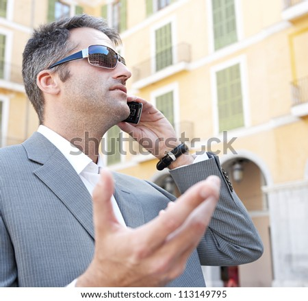 Portrait of a businessman using a smart phone to have a conversation while standing in front of classic office buildings in the city. - stock photo
