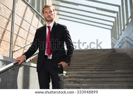 Portrait of a businessman walking down the stairs - stock photo