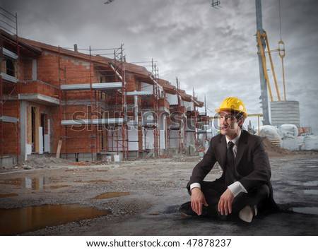 Portrait of a businessman wearing a helmet and sitting in a construction site - stock photo