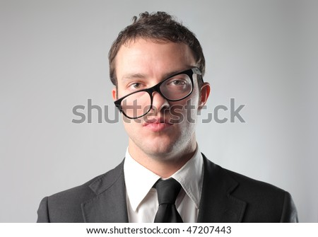 Portrait of a businessman wearing crosswise glasses - stock photo