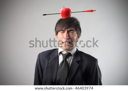 Portrait of a businessman with an apple pierced by an arrow on his head - stock photo