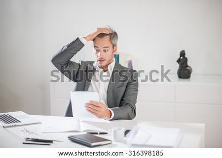 Portrait of a businessman with grey hair and beard having a hard time with some ideas. He is sitting at his desk, holding his head with his hand looking at his tablet like if he was having a bad news - stock photo
