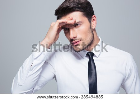 Portrait of a businessman with headache over gray background - stock photo