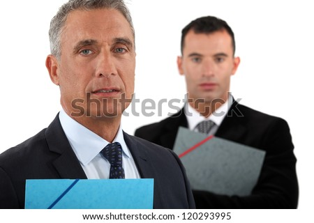 Portrait of a businessman with his assistant trailing behind him - stock photo