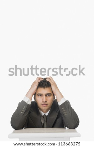 Portrait of a businessman with his head in hands - stock photo