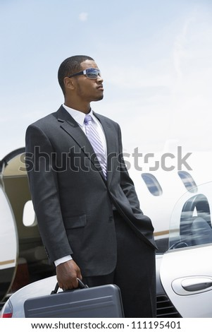 Portrait of a businessman with luggage at the airfield - stock photo