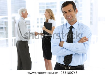 Portrait of a businessman with partners talking on background - stock photo