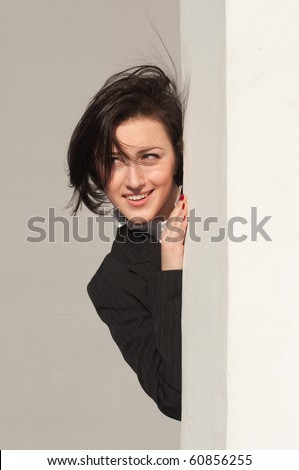 Portrait of a businesswoman behind the corner - stock photo