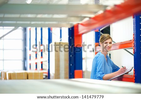 Portrait of a businesswoman  controlling inventory in a warehouse - stock photo