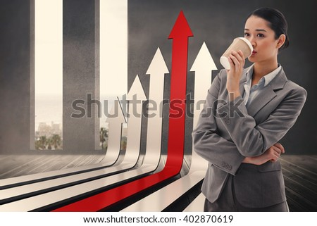 Portrait of a businesswoman drinking a takeaway tea against grey room with windows showing the ocean - stock photo