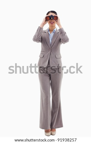 Portrait of a businesswoman looking through binoculars against a white background - stock photo