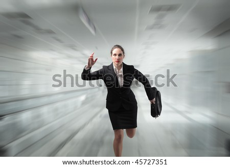Portrait of a businesswoman running in an office hall