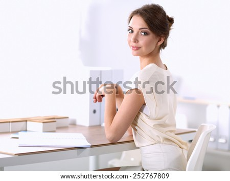 Portrait of a businesswoman sitting at a desk with a laptop . - stock photo