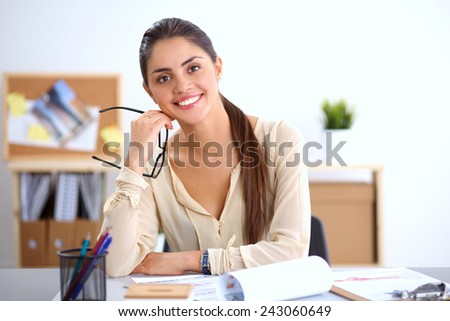 Portrait of a businesswoman sitting at a desk with a laptop, isolated - stock photo