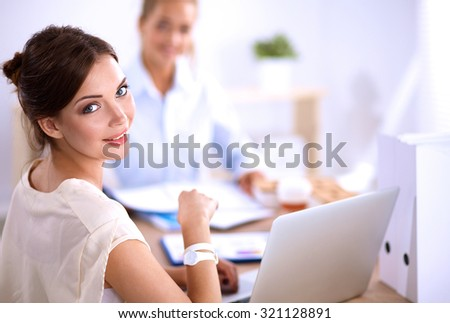 Portrait of a businesswoman sitting at  desk with  laptop - stock photo