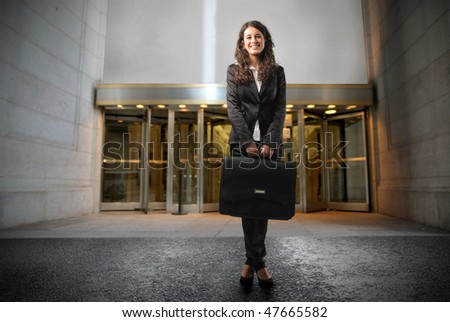 Portrait of a businesswoman standing in front of the entrance of a building - stock photo
