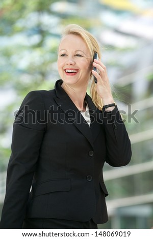 Portrait of a businesswoman talking on mobile phone outdoors - stock photo