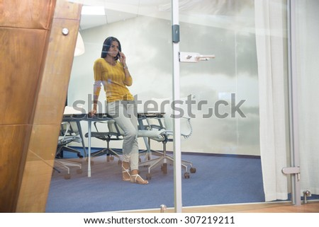 Portrait of a businesswoman talking on the phone in office - stock photo