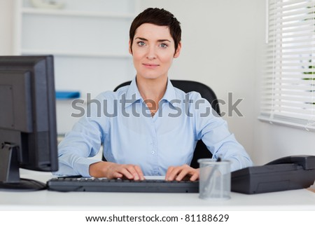 Portrait of a businesswoman typing with her computer while looking at the camera
