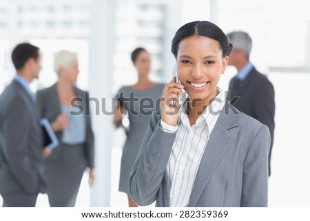 Portrait of a businesswoman using mobile phone with colleagues behind - stock photo