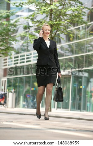 Portrait of a businesswoman walking and talking on mobile phone in the city - stock photo