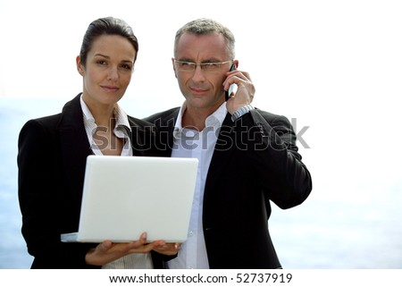 Portrait of a businesswoman with a laptop computer and a businessman with a phone - stock photo