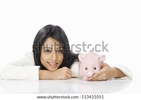 Portrait of a businesswoman with a piggy bank - stock photo