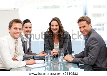 Portrait of a businesswoman with her team sitting at a table - stock photo