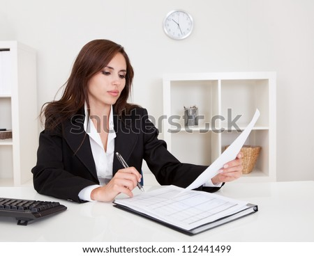 Portrait of a businesswoman with paperwork at office desk - stock photo