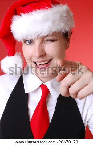 portrait of a businesswoman with santa hat is pointing at you