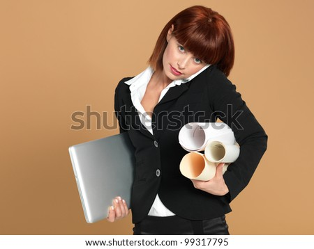 portrait of a bussy, young businesswoman, holding a laptop and some papers, talking on the telephone, on beige background
