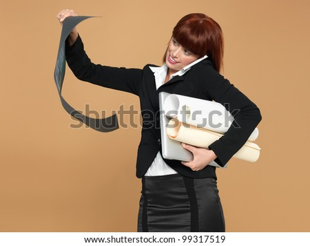 portrait of a bussy, young woman architect, holding a laptop and a blueprint, talking on the telephone, on beige background - stock photo