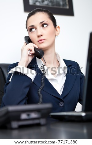 portrait of a busy businesswoman talking on phone in her office - stock photo