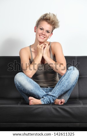 Portrait of a candid fashion woman sitting on a couch at home with crossed legs - stock photo