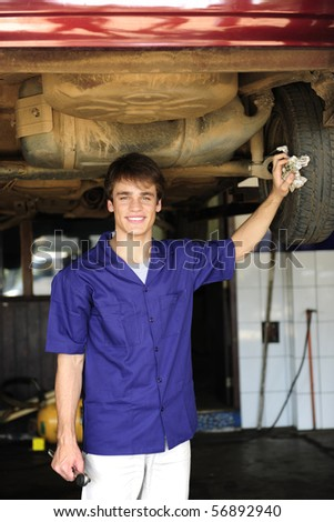 portrait of a car mechanic at work at the car  repair  shop - stock photo