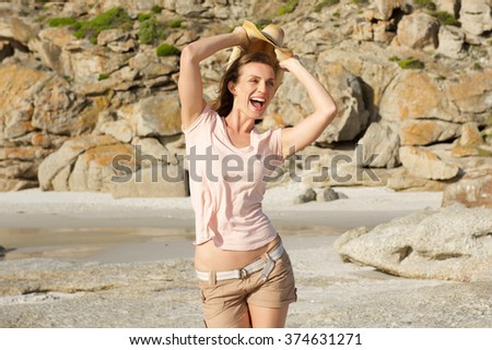 Portrait of a carefree woman enjoying the beach - stock photo