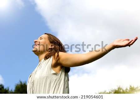 Portrait of a carefree woman smiling with arms spread open  - stock photo