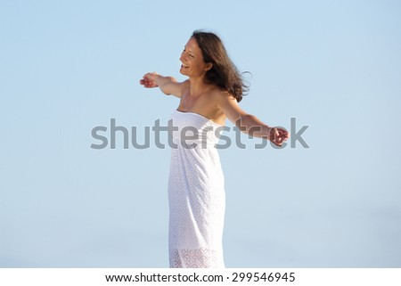 Portrait of a carefree woman standing outside with arms spread open - stock photo