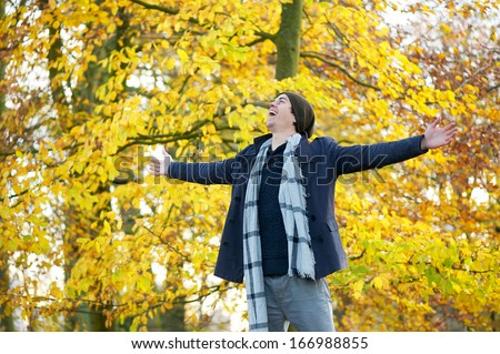 Portrait of a carefree young man standing outdoors with open arms - stock photo