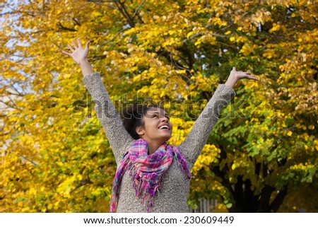 Portrait of a carefree young woman enjoying autumn with arms raised - stock photo