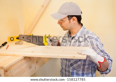 Portrait of a carpenter cutting wood - stock photo
