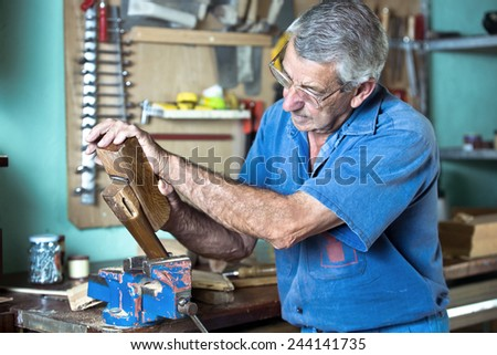 Portrait of a carpenter planing a piece of wood in the workshop of his house / cabinetmaker working with plane in the bench in garage at home - stock photo