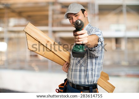 Portrait of a carpenter wood planks and a drill in a construction site - stock photo